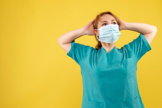 Vista frontal da jovem médica em traje médico e máscara estéril na parede amarela