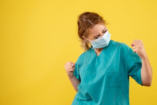 Vista frontal da jovem médica em traje médico e máscara estéril regozijando-se na parede amarela