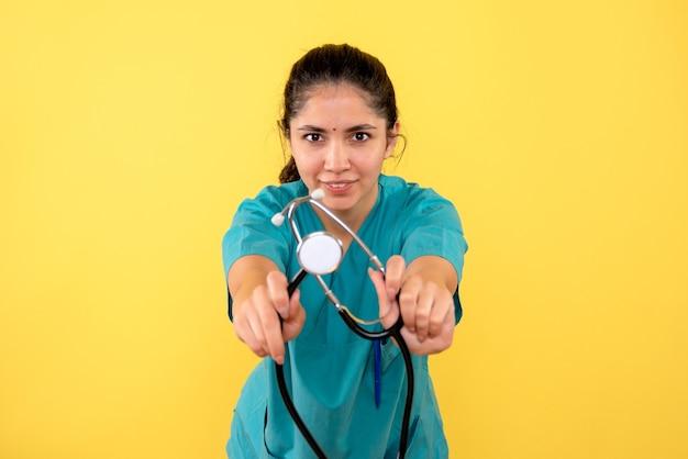 Vista frontal da jovem médica mostrando o estetoscópio na parede amarela