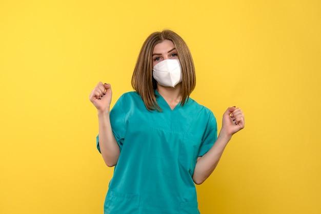 Vista frontal da jovem médica na parede amarela