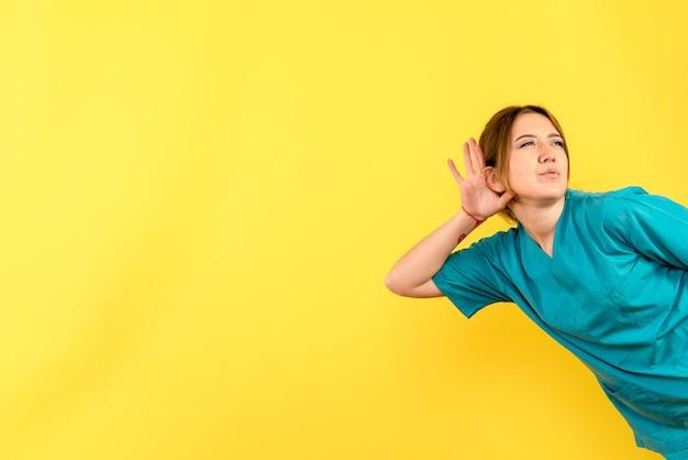 Vista frontal da jovem médica ouvindo na parede amarela