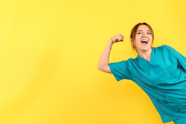 Vista frontal da jovem médica regozijando-se na parede amarela