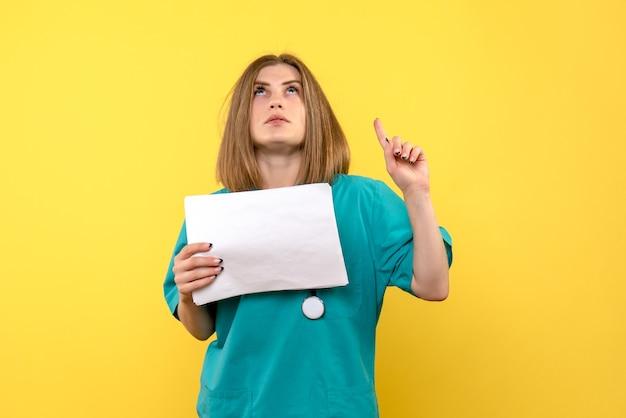 Vista frontal da jovem médica segurando arquivos na parede amarela