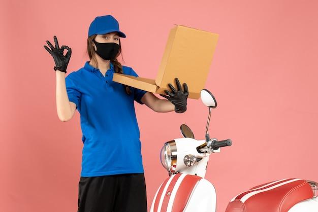 Vista frontal da jovem mensageira usando luvas de máscara médica, em pé ao lado da caixa de abertura da motocicleta, fazendo gesto de óculos no fundo cor de pêssego pastel