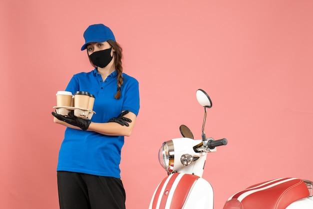 Vista frontal da jovem mensageira usando luvas de máscara médica em pé ao lado de uma motocicleta segurando pequenos bolos de café em um fundo de cor pastel de pêssego