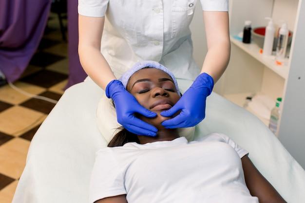 Vista frontal da jovem mulher africana relaxante na cama de massagem, recebendo massagem facial no spa de beleza.
