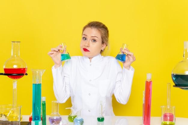 Vista frontal da jovem química feminina em um terno branco em frente à mesa com soluções de ed, trabalhando com eles no trabalho de química do espaço amarelo