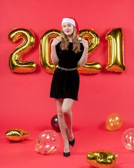 Vista frontal da jovem senhora vestida de preto colocando as mãos nos ombros de balões em foto vermelha de natal