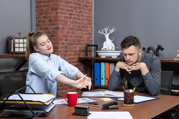 Vista frontal da jovem trabalhadora e seu colega de trabalho sentado, sentindo-se cansado à mesa no escritório