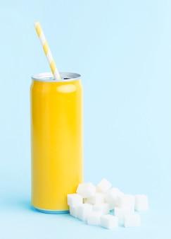Vista frontal da lata de refrigerante com canudo e cubos de açúcar