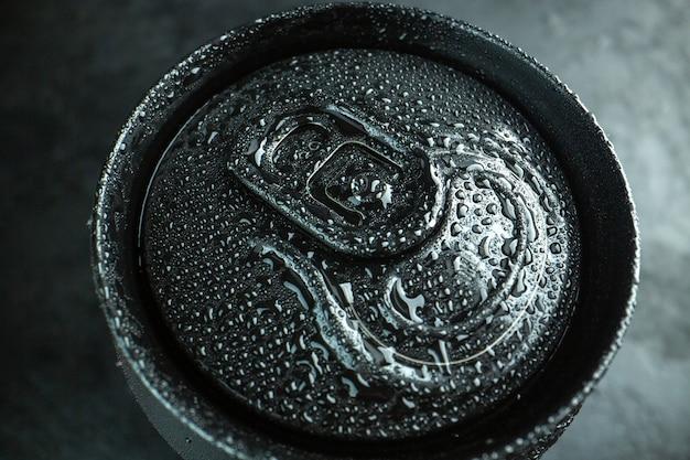 Vista frontal da lata de refrigerante na água escura da foto da bebida