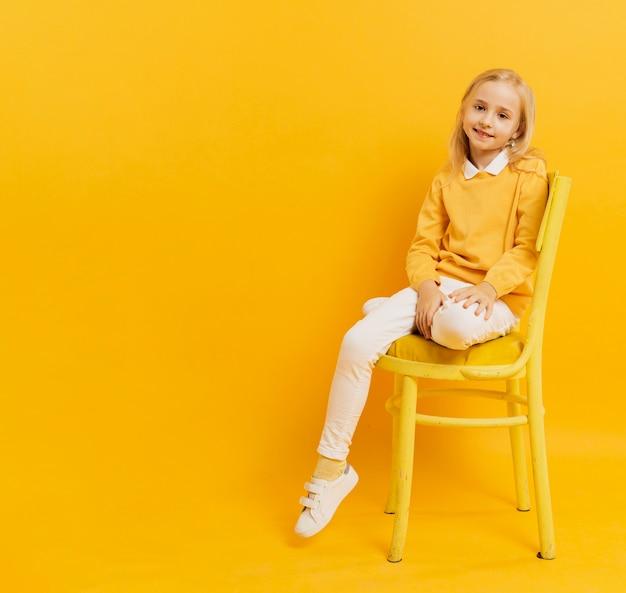 Vista frontal da linda garota posando enquanto está sentado na cadeira