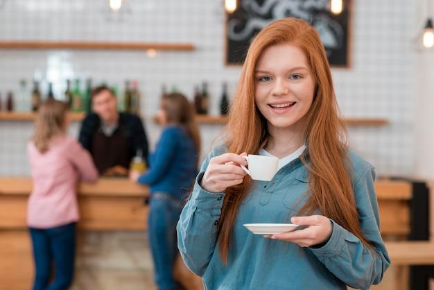 Vista frontal da linda garota tomando café