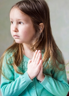 Vista frontal da linda garotinha rezando