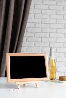Vista frontal da lousa de menu com garrafa de vinho