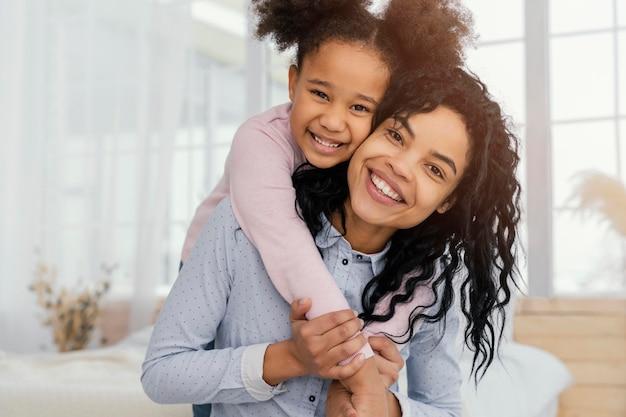 Vista frontal da mãe brincando em casa com a filha