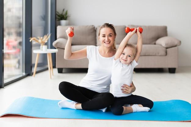 Vista frontal da mãe com a filha posando enquanto segura pesos