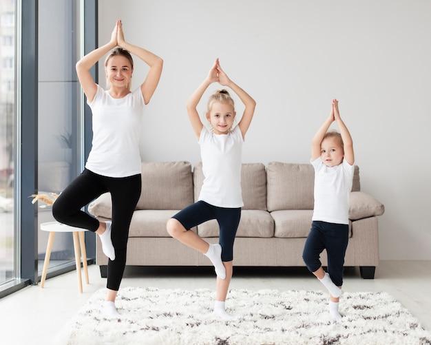 Vista frontal da mãe com filhas em casa exercitando