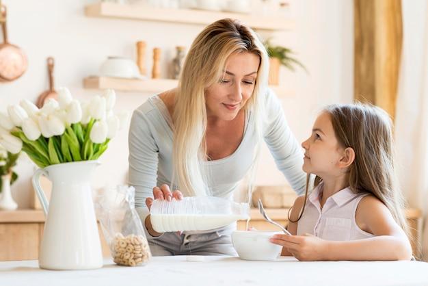 Vista frontal da mãe derramando leite sobre os cereais da filha