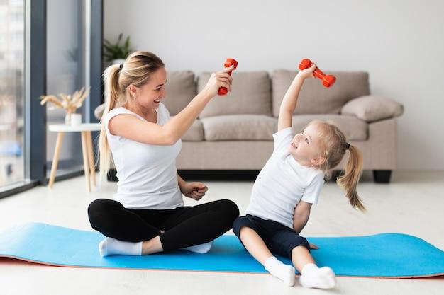 Vista frontal da mãe e da criança exercitando com pesos em casa