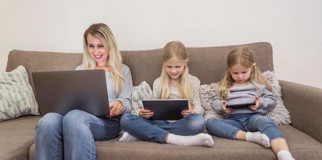 Vista frontal da mãe e das filhas com tecnologia