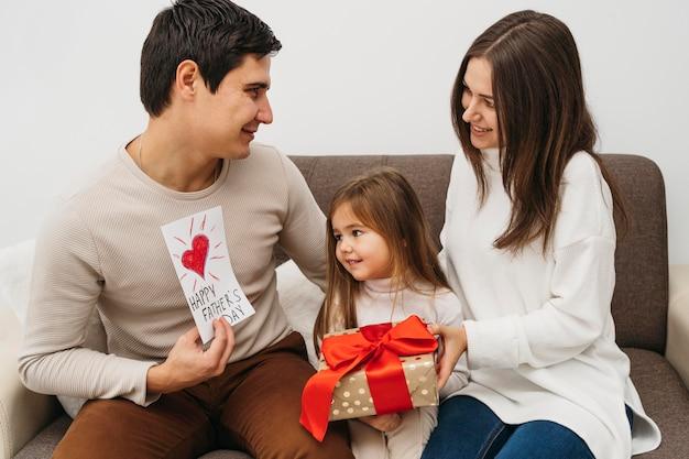 Vista frontal da mãe e do pai com a filha e um presente em casa