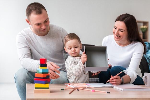 Vista frontal da mãe e do pai com o filho em casa