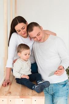 Vista frontal da mãe e do pai olhando para celular com criança