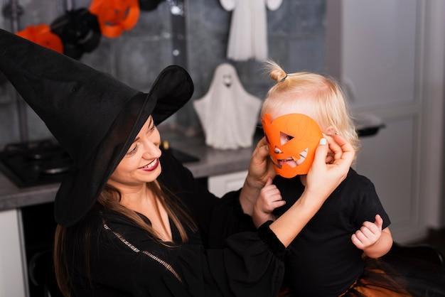 Vista frontal da mãe e filha com máscara de abóbora