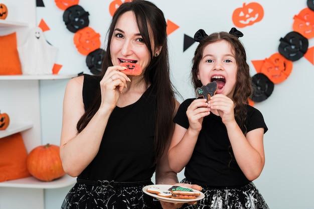 Vista frontal da mãe e filha comendo biscoitos