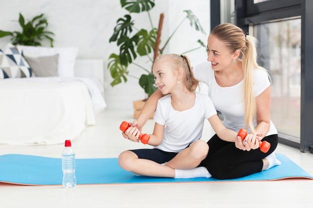 Vista frontal da mãe e filha exercitar com pesos em casa