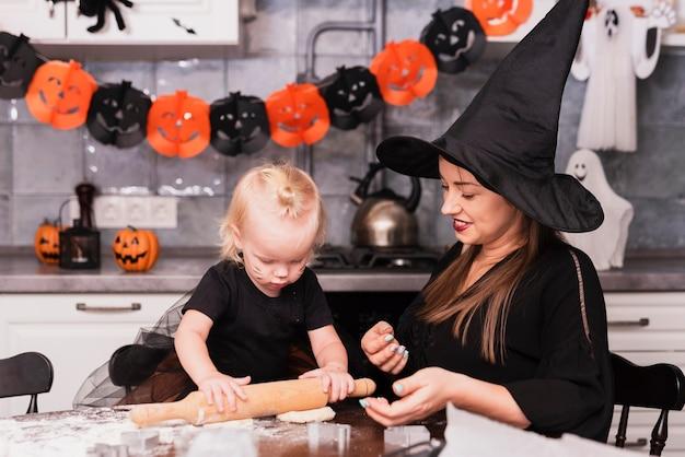 Vista frontal da mãe e filha fazendo biscoitos