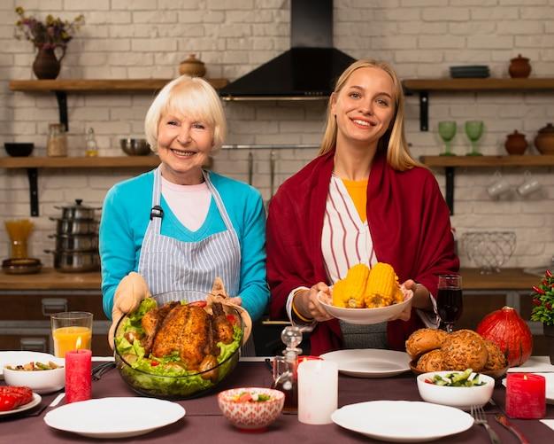 Vista frontal da mãe e filha segurando a comida