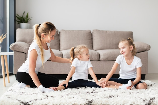 Vista frontal da mãe e filhas em casa exercitando