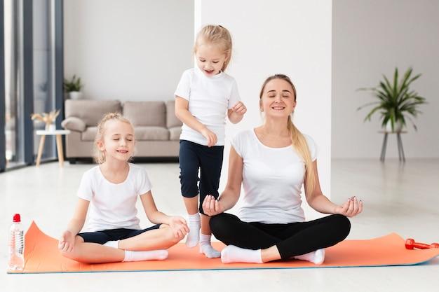 Vista frontal da mãe e filhas praticando ioga em casa