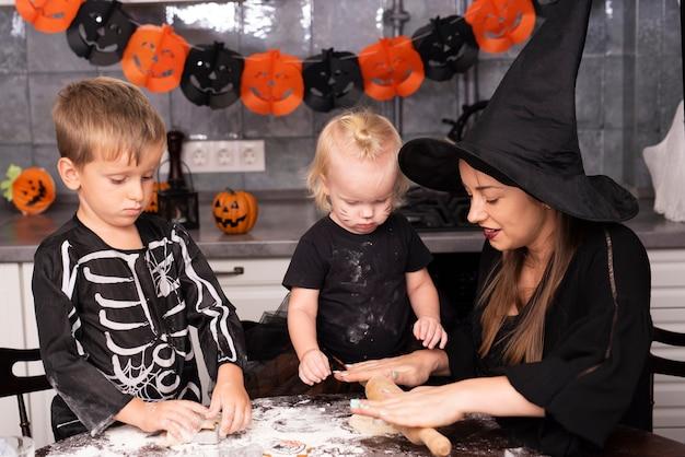 Vista frontal da mãe e filhos fazendo biscoitos