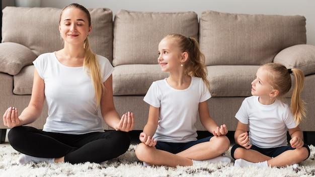 Vista frontal da mãe fazendo yoga com filhas em casa
