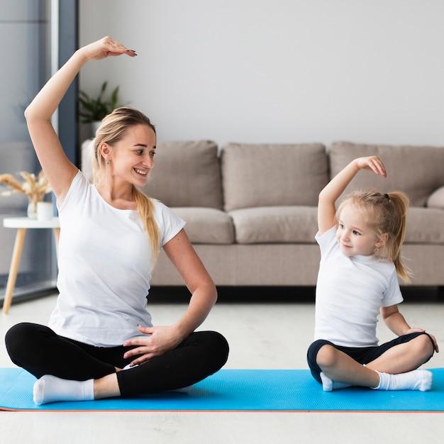Vista frontal da mãe feliz, exercitar-se com a filha em casa