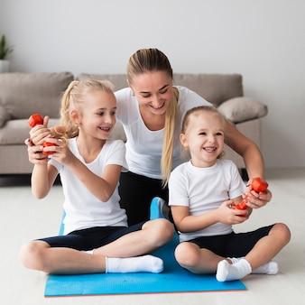 Vista frontal da mãe posando com filhas em casa, mantendo pesos