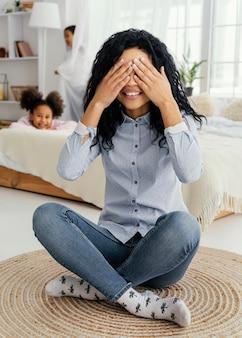 Vista frontal da mãe sorridente brincando de esconde-esconde com os filhos em casa