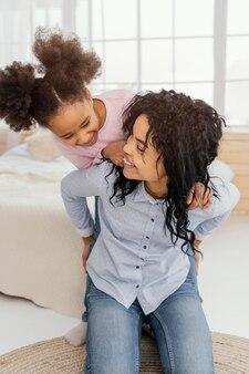 Vista frontal da mãe sorridente brincando em casa com a filha