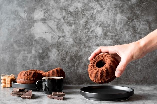 Vista frontal da mão colocando bolo de chocolate no prato