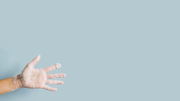 Vista frontal da mão com espuma de sabão