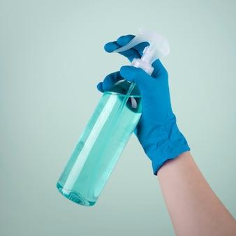 Vista frontal da mão com luva cirúrgica usando desinfetante