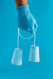 Vista frontal da mão com luva segurando copos plásticos com barbante