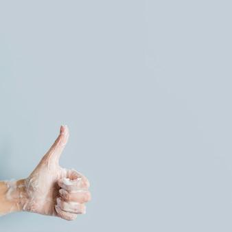 Vista frontal da mão com sabão desistindo polegares