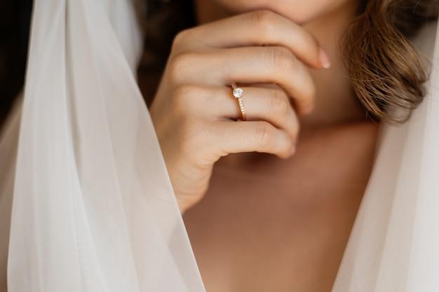 Vista frontal da mão da noiva com um anel de noivado perto do pescoço e véu de noiva