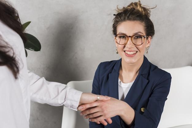 Vista frontal da mão de uma mulher, apertando a pessoa de recursos humanos