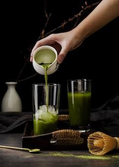 Vista frontal da mão derramando chá matcha em vidro na bandeja