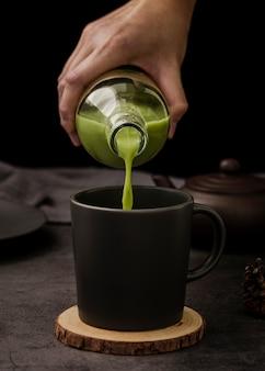 Vista frontal da mão derramando matcha chá na xícara
